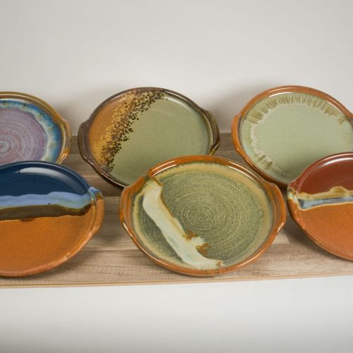 a group of round serving trays in 6 different patterns.