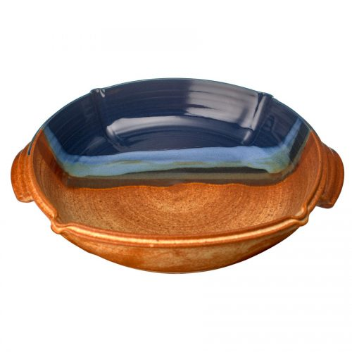 a large, blue and sandy brown square baking dish with handles