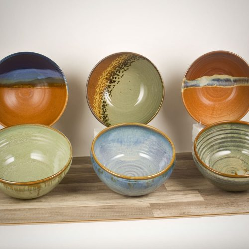 6 deep serving bowls with rounded sides in assorted patterns.