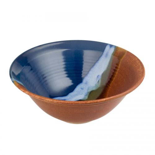 a large, blue and sandy brown serving bowl