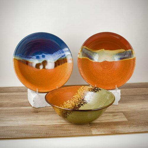 3 deep serving bowls with flared rims, in assorted patterns.