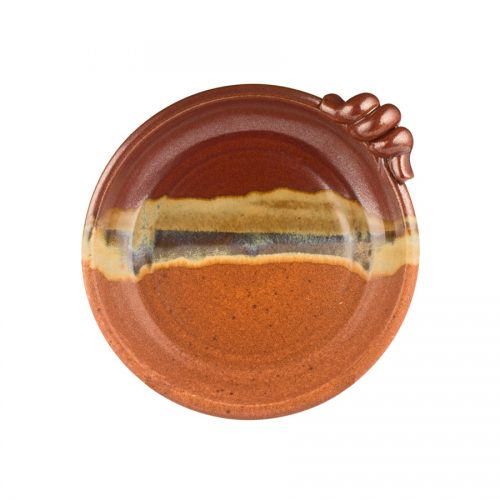 a round, red and sandy brown baking plate with a knob