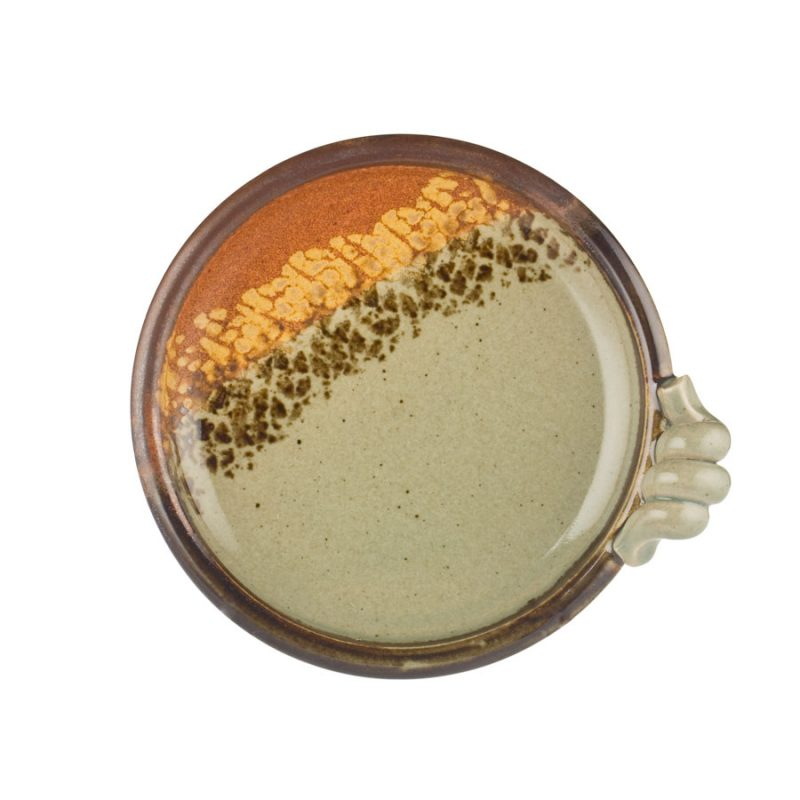 a round, green and sandy brown baking plate with a knob