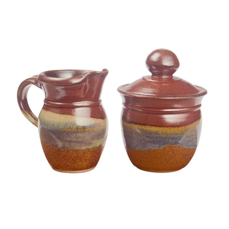 a small, red and sandy brown cream pitcher and sugar jar set