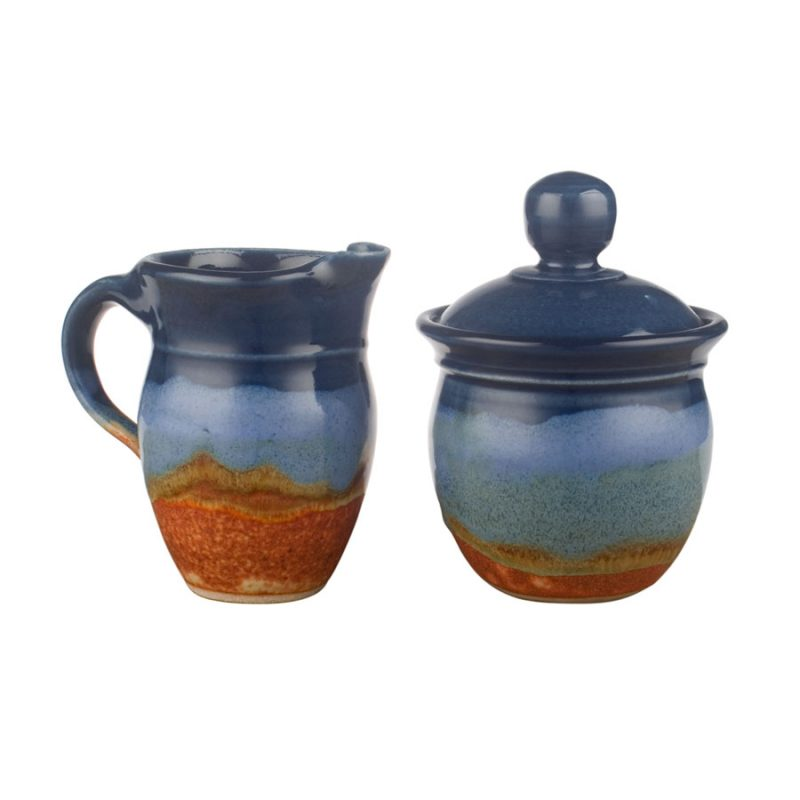 a small, blue and sandy brown cream pitcher and sugar jar set