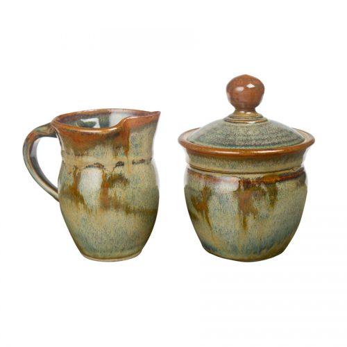 a small, green cream pitcher and sugar jar set