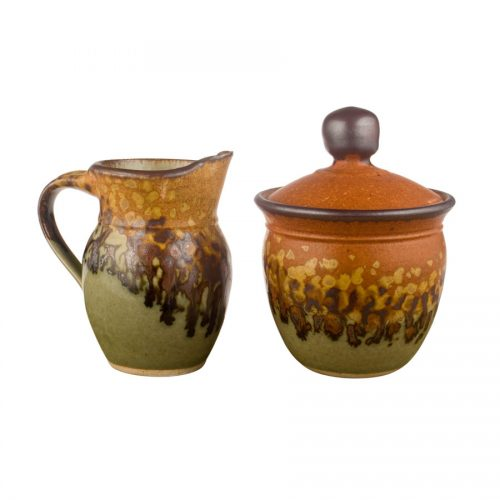 a small, green and sandy brown cream pitcher and sugar jar set