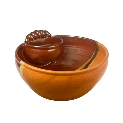 a large, red and sandy brown serving bowl with an attached cup and handle