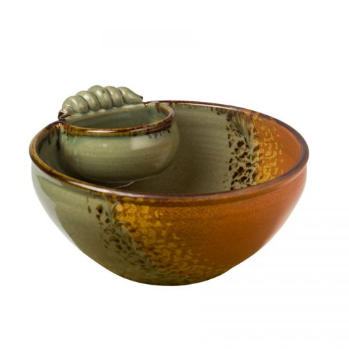 a large, green and sandy brown serving bowl with an attached cup and handle