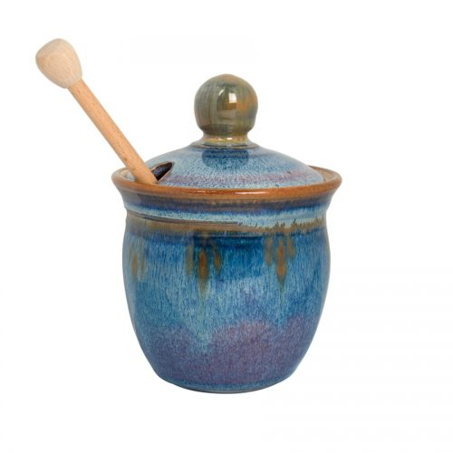 a small, blue honey storage jar with a lid