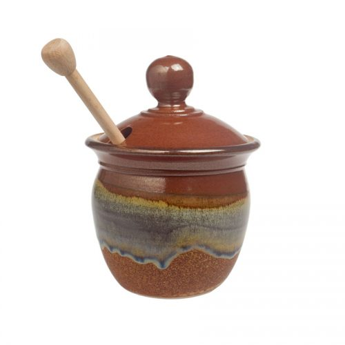 a small, red and sandy brown honey storage jar with a lid