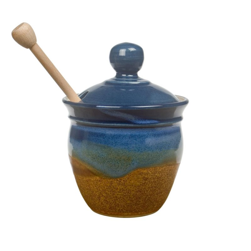 a small, blue and sandy brown honey storage jar with a lid