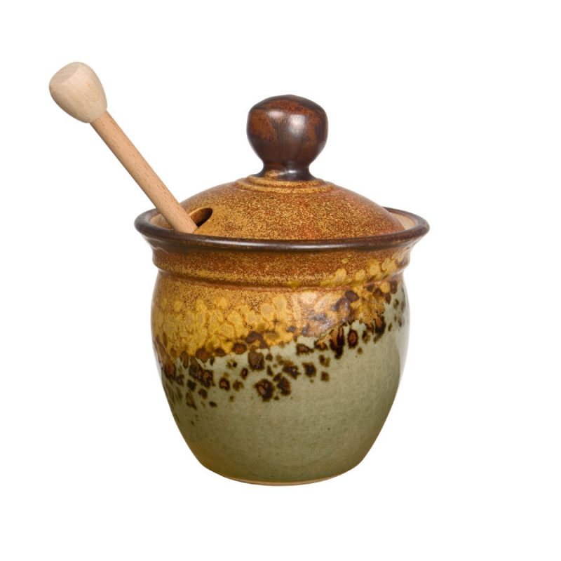 a small, green and sandy brown honey storage jar lid
