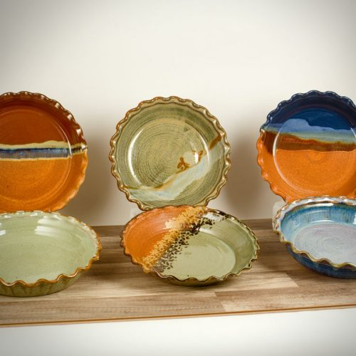 6 shallow pie baking dishes with frilled edges, in assorted patterns.