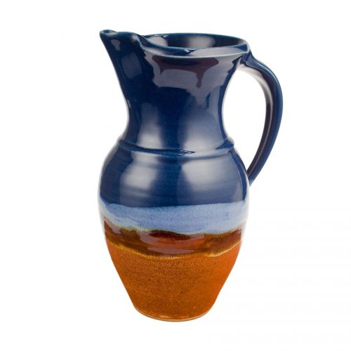 a tall, blue and sandy brown pitcher with a handle