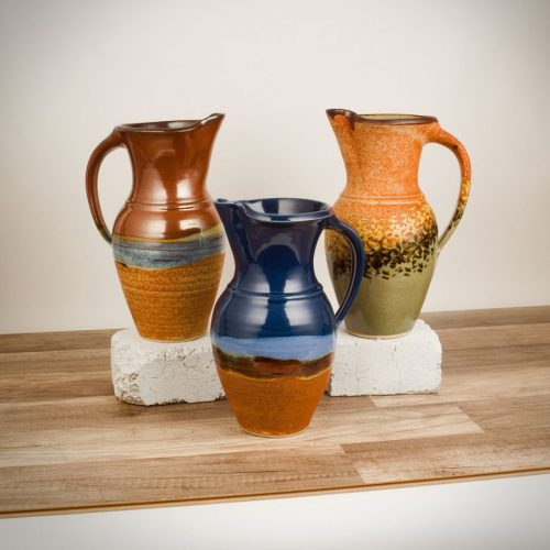 3 pitchers with handles, in assorted patterns.