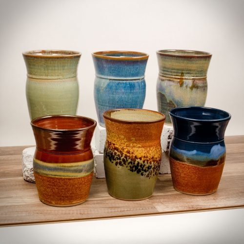 6 tall kitchen storage jars in assorted patterns.