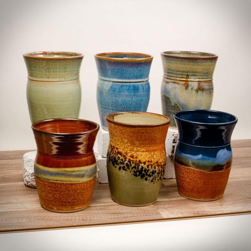 6 tall kitchen storage jars in assorted patterns.