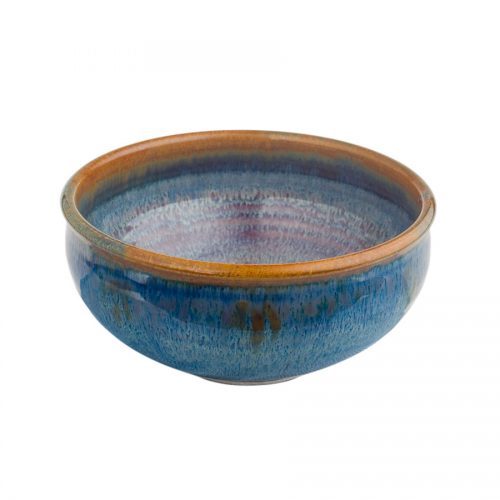A small, variegated blue dinnerware bowl with rounded sides and a bronze colored rim.