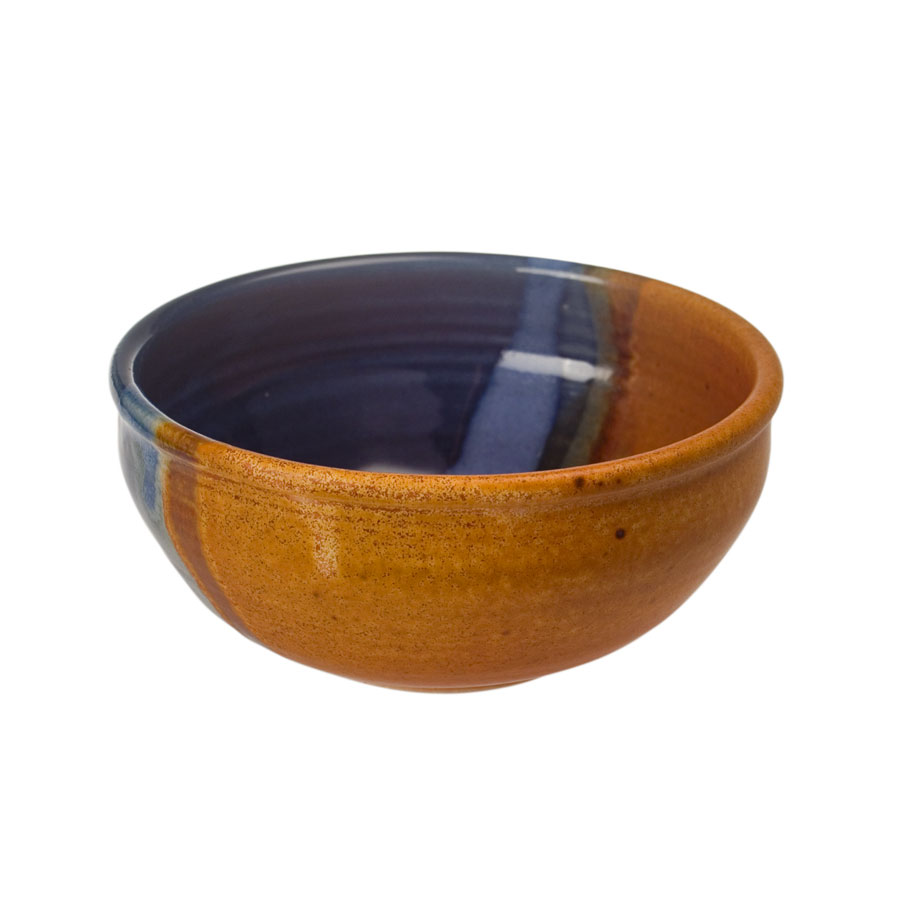 A small, handmade, blue and sandy brown dinnerware bowl with rounded sides and a sky blue band across the surface.