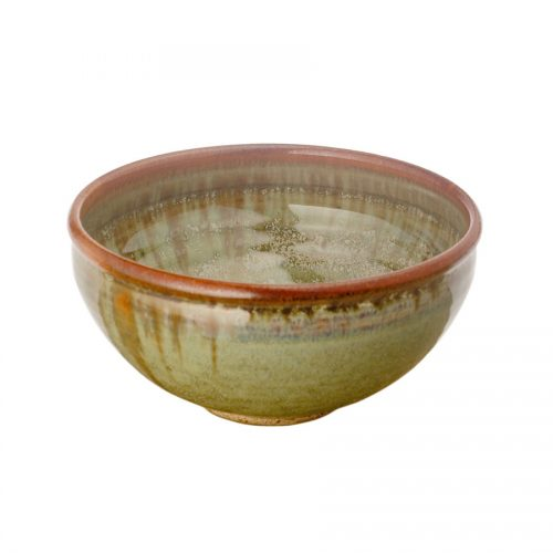 A small, handmade, frosted mint green dinnerware bowl with rounded sides and a bronze colored rim.