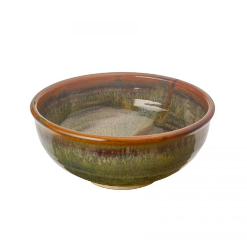 A small, handmade, variegated green dinnerware bowl with rounded sides and a bronze colored rim, featuring a light blue band across the surface.