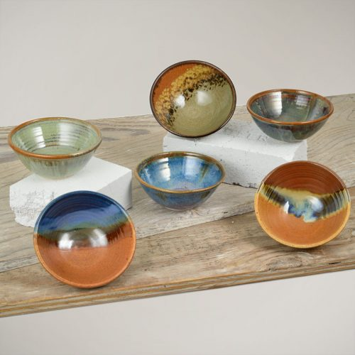Six small dinnerware bowls with flared sides in six different patterns.
