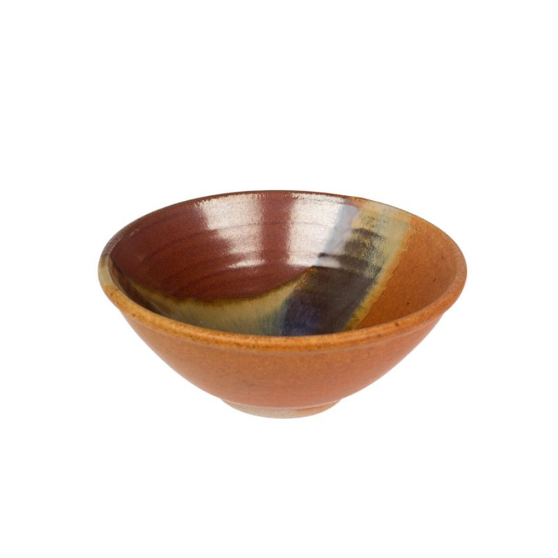 a petite, handmade, red and sandy brown dinnerware bowl with flared sides and a variegated blue band across the surface.