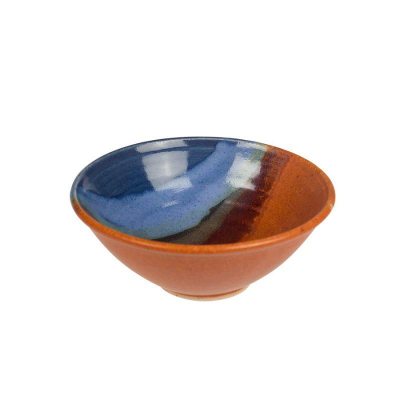 A petite, handmade, blue and orange dinnerware bowl with flared sides and a sky blue band across the surface.