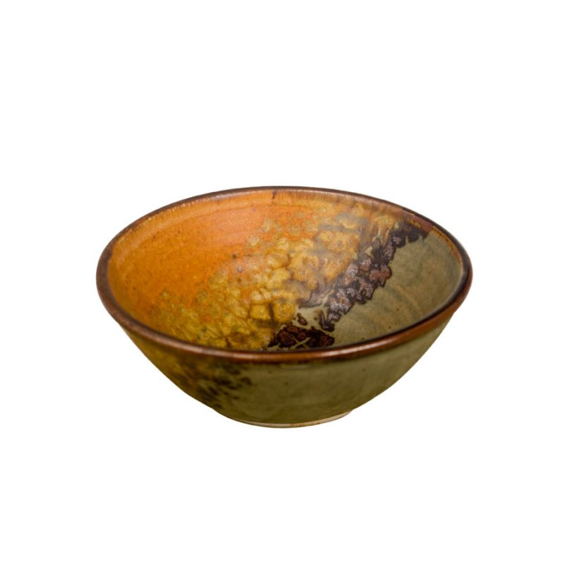 A petite, handmade, green and orange dinnerware bowl with flared sides and a dark brown rim, featuring a black and gold animal print band across the surface.
