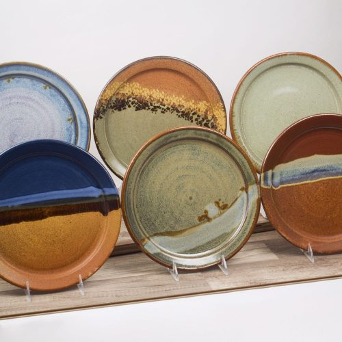 a group shot of 6 handmade dinner plates, each in a different pattern.