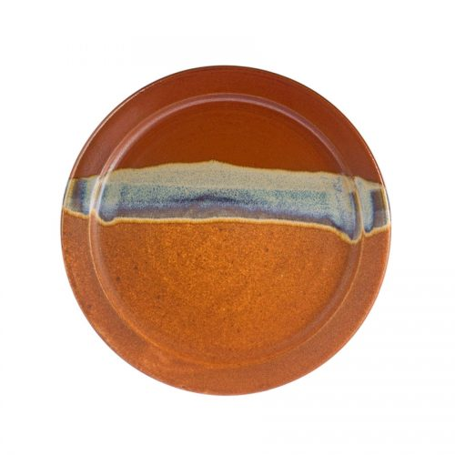 a large, handmade, red and sandy brown dinnerware plate with a variegated blue band across the surface.