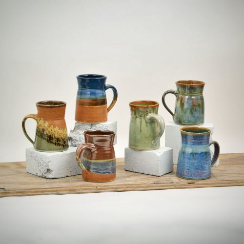 Six coffee mugs with tapered sides and a flared lip. Each one is in a different pattern.