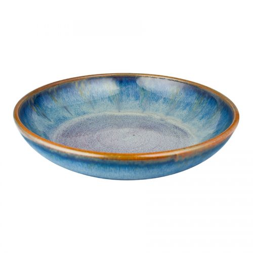 A shallow, handmade, variegated blue serving bowl with a bronze colored rim.