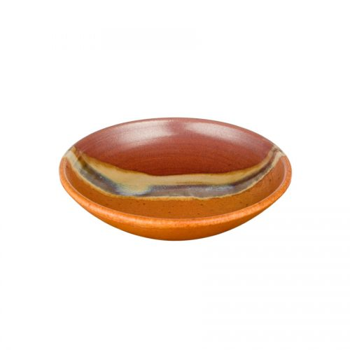 A small, shallow, handmade dinnerware bowl for pasta or salad. It is red and orange with a pale blue band across a third of the pottery.