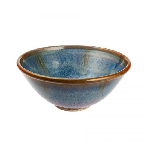 a small, handmade, variegated blue dinnerware bowl with flared sides and a bronze colored rim.