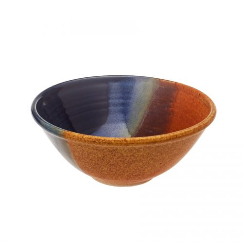 a small, handmade, blue and orange salad bowl with flared sides and a sky blue band across the surface.