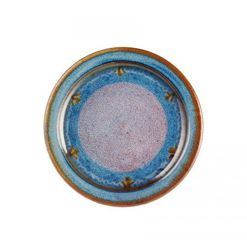 A small, handmade, variegated blue dinnerware plate with a bronze colored rim.