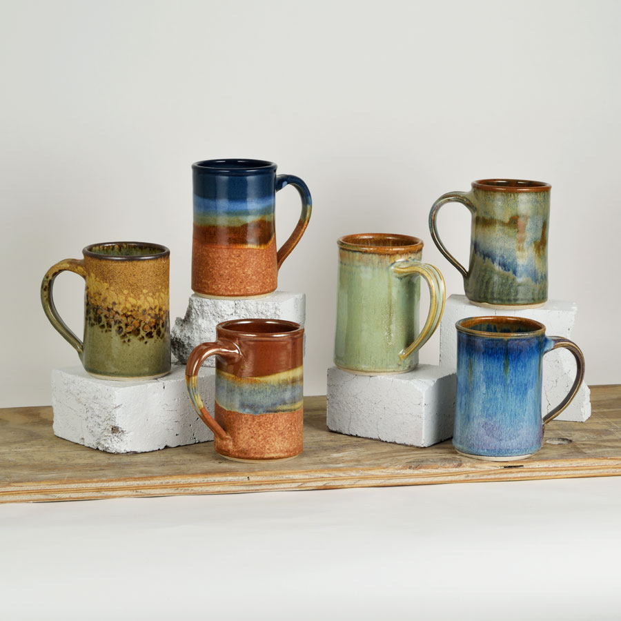 Six straight sided coffee mugs with handles in assorted patterns.