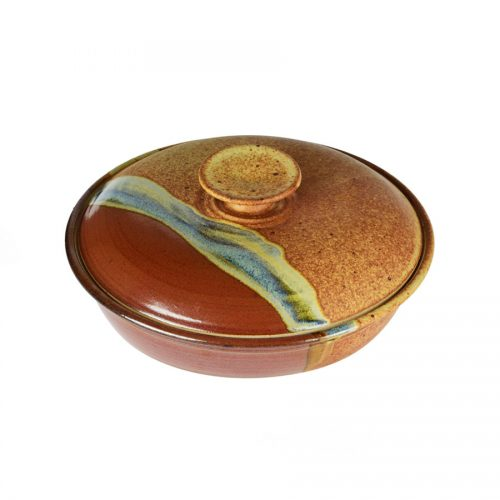 A shallow, handmade, red and orange dish with a lid for warming tortillas or bread,