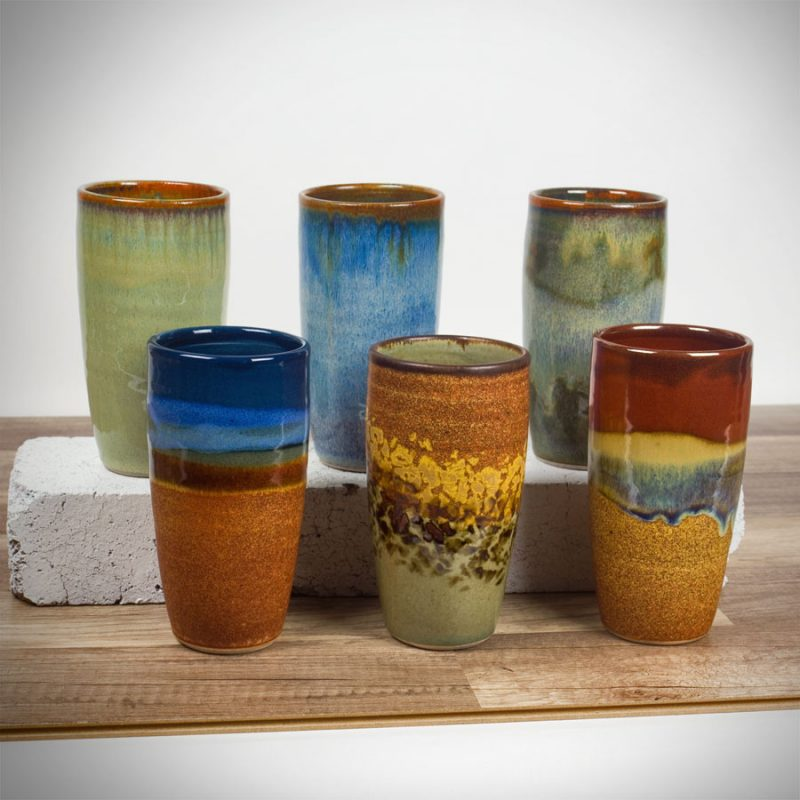 Six tall, slender, handmade drinking cup in assorted patterns.