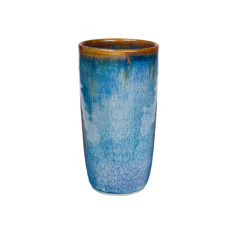 A tall, handmade, variegated blue drinking cup with a bronze colored rim.