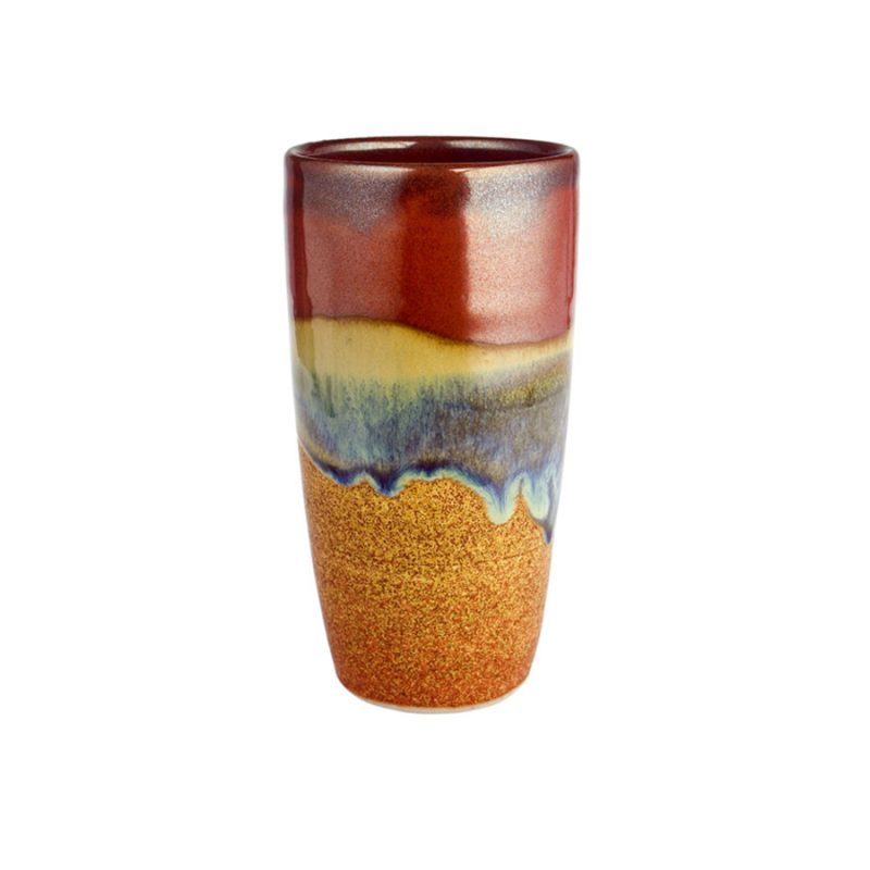 A tall, handmade, red and orange drinking cup with a variegated blue band across the surface.