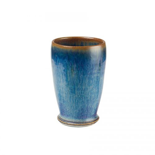 A short, handmade, variegated blue drinking cup with a bronze colored rim.