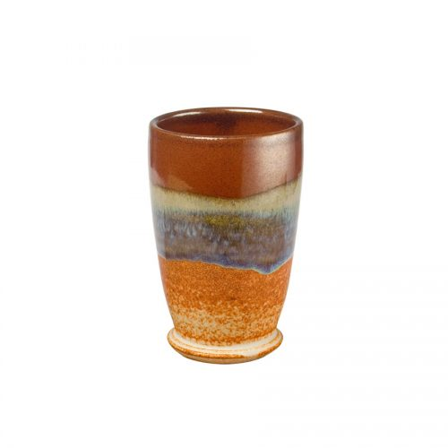 A short, handmade, red and sandy brown drinking cup with a variegated blue band across the surface.