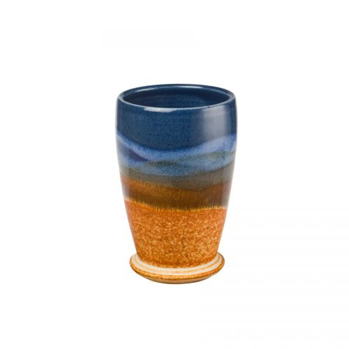 a short, blue and sandy brown drinking cup