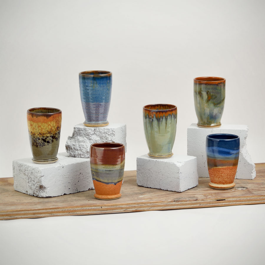 Six short, handmade, drinking cups for wine and juice, each in a different pattern.