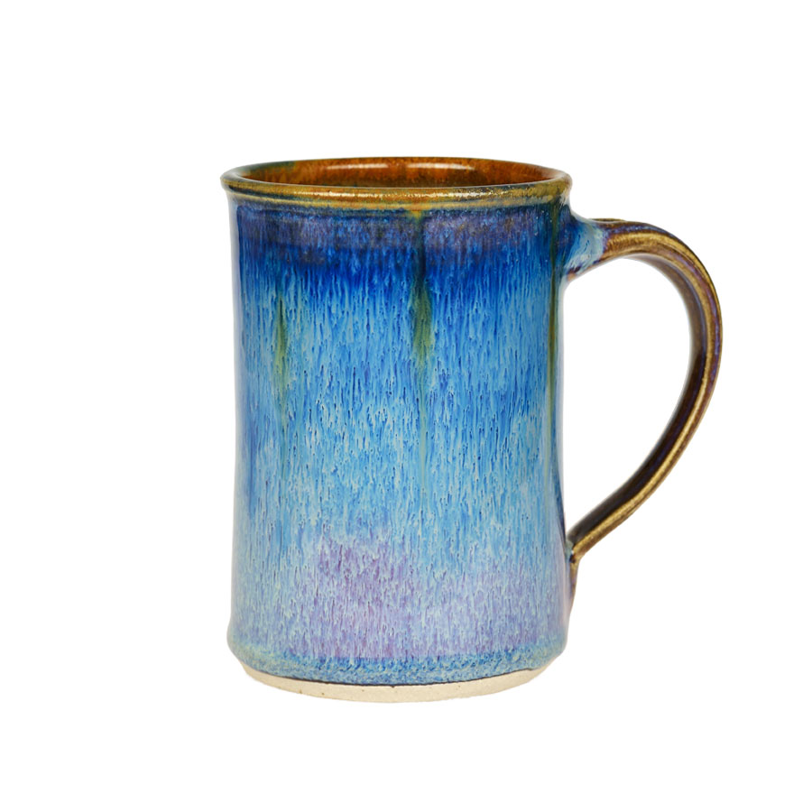 A handmade, variegated blue coffee mug with straight sides and a bronze colored rim.