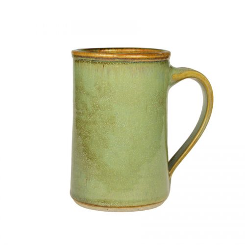 A handmade mint green coffee mug with straight sides and a bronze colored rim.