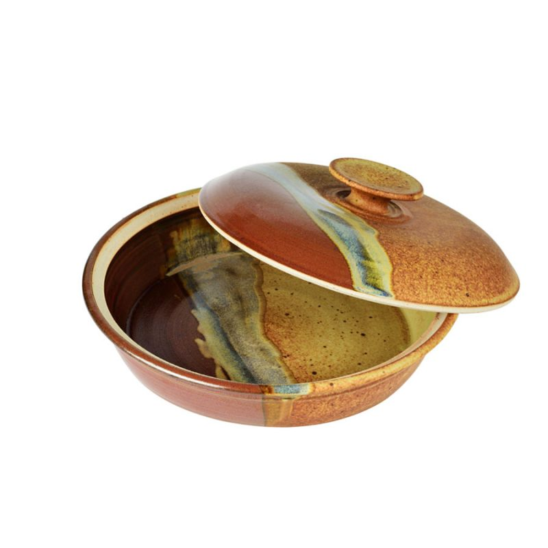 A shallow, handmade, red and orange dish with a lid for warming tortillas or bread.